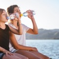 Two girls drinking water and sitting by the sea