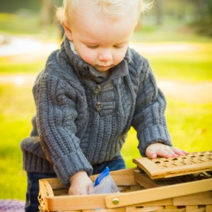 Adorable Little Blonde Baby Boy Opening a Picnic Basket Outdoors at the Park.
