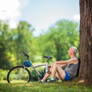 Senior cyclist sitting by a tree in park