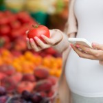 pregnant woman with smartphone at street market