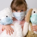 Sick young girl in surgical mask with stuffed animals
